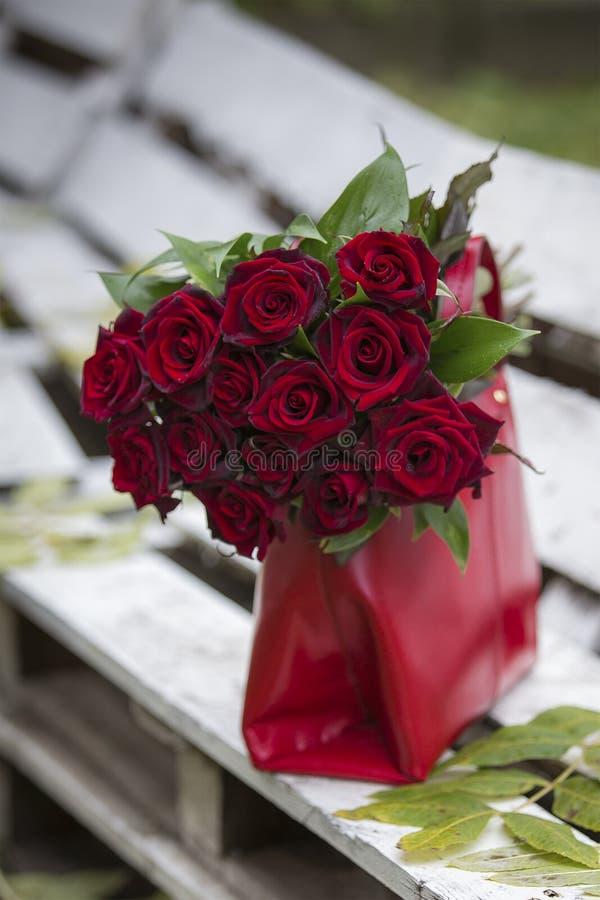 在红色小包的红色玫瑰 库存照片