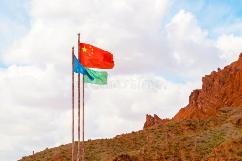 在红色山新疆的中国旗子 免版税图库摄影