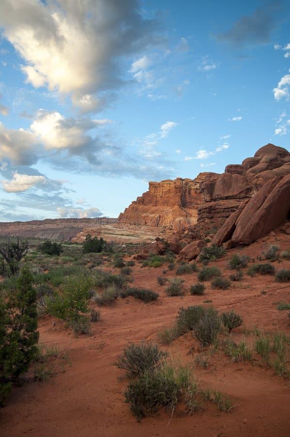 在红色岩石墙壁上的清早日出 免版税库存照片