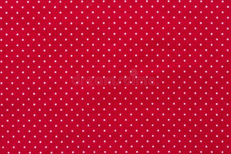 在红色帆布棉花纹理,织品背景的圆点 库存照片