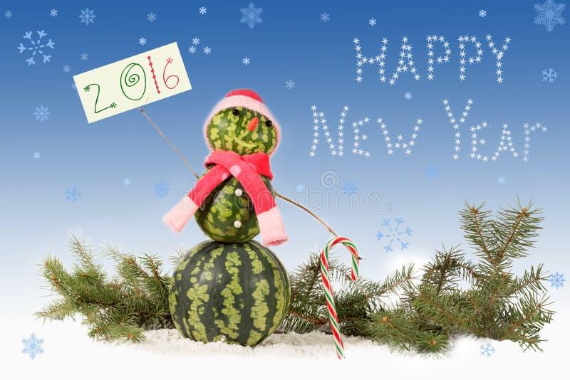 在红色帽子和围巾的雪人有在蓝色背景和落的雪花的棒棒糖的与题字2016年 库存图片
