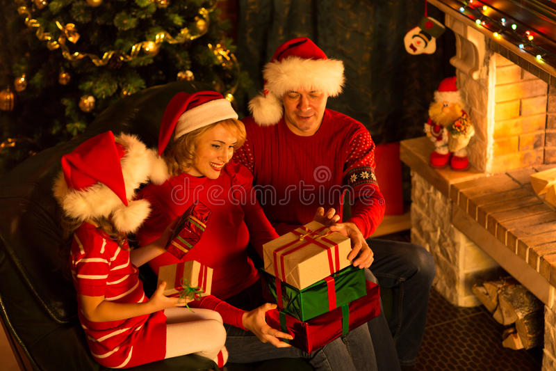 在红色帽子的圣诞节家庭有礼物盒的 库存图片