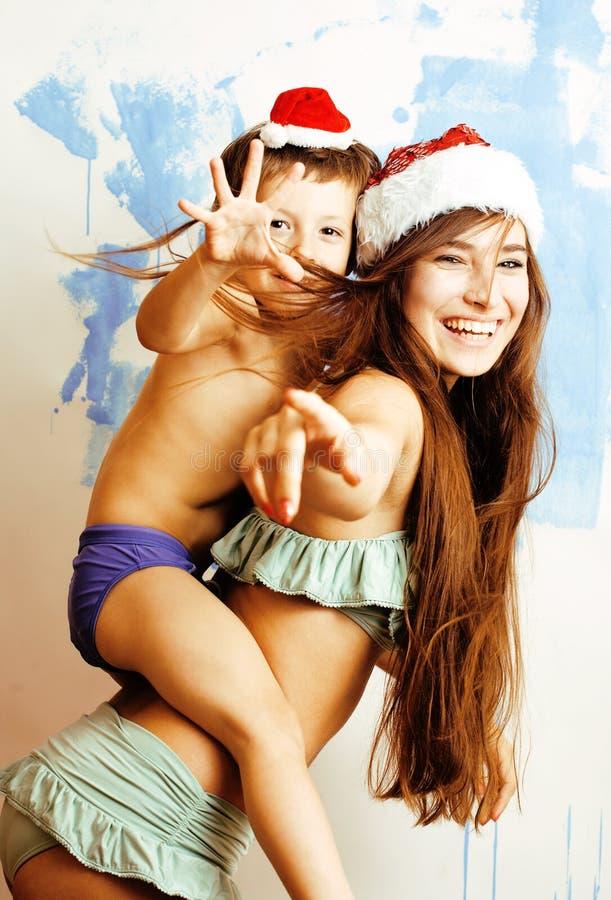 在红色帽子的滑稽的家庭庆祝新年,有儿子愉快微笑的,生活方式人概念母亲的 免版税库存图片