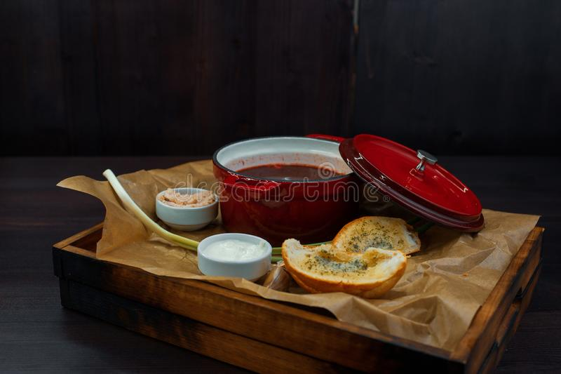 在红色平底深锅的鲜美热的红色甜菜汤用大蒜、大葱、酸性稀奶油和白面包在一个木板 免版税库存照片