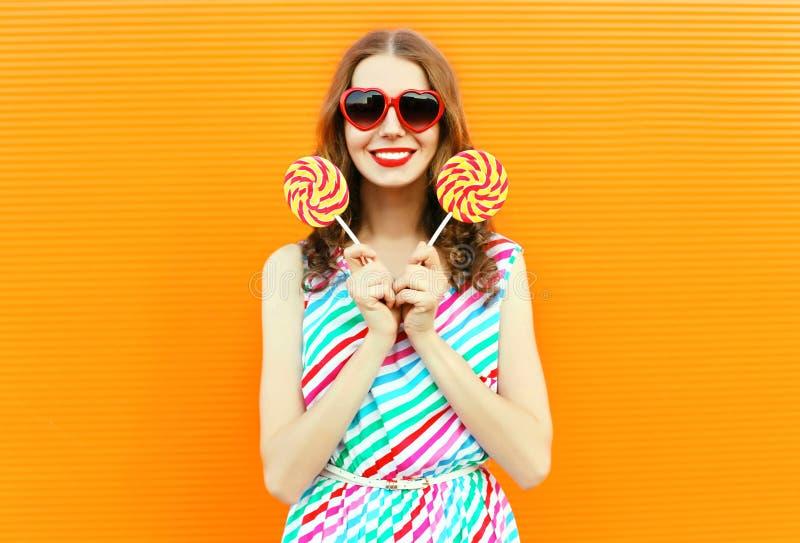 在红色心形的太阳镜的愉快的微笑的妇女藏品棒棒糖,在橙色墙壁上的五颜六色的镶边礼服 库存照片
