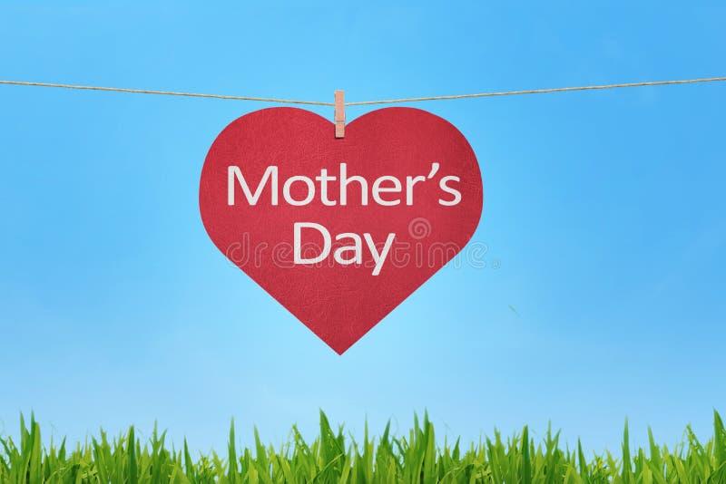 在红色心形的礼物写的愉快的母亲节消息标记 免版税库存照片