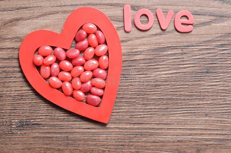 在红色心脏显示的红色软心豆粒糖塑造以词爱 库存图片