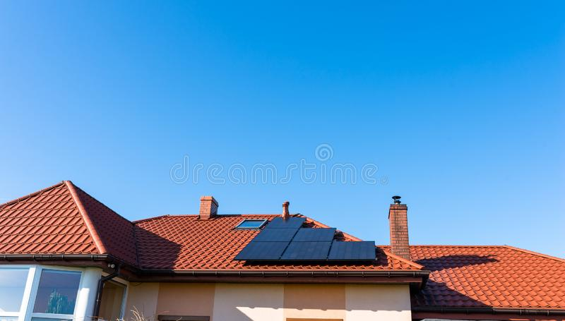 在红色房子屋顶的太阳电池板在天空蔚蓝背景中  免版税库存照片