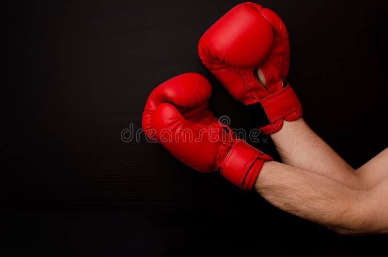 在红色拳击手套的手在框架的角落在黑背景的,空的空间 免版税库存图片
