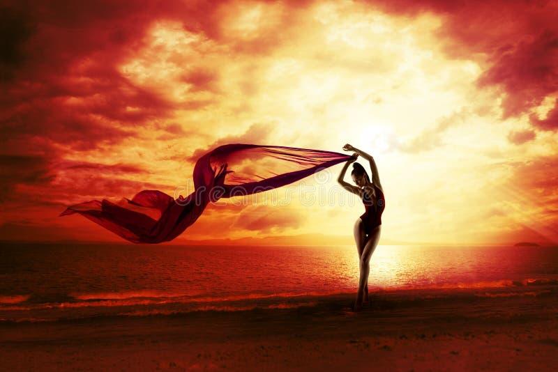 在红色日落天空,肉欲的女性海滩的性感的妇女剪影 库存图片