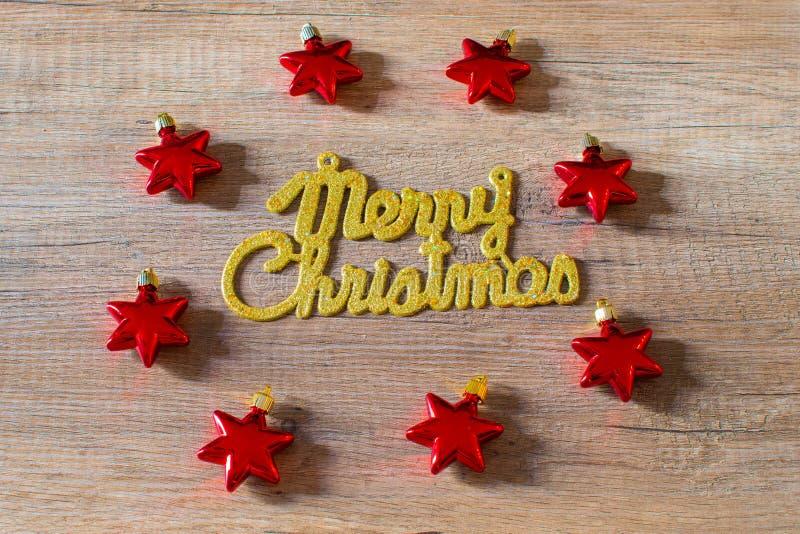 在红色星装饰品围拢的木背景的圣诞快乐金黄文本 免版税图库摄影