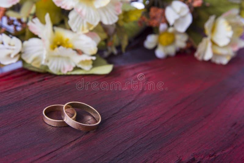 在红色木背景的婚戒 图库摄影