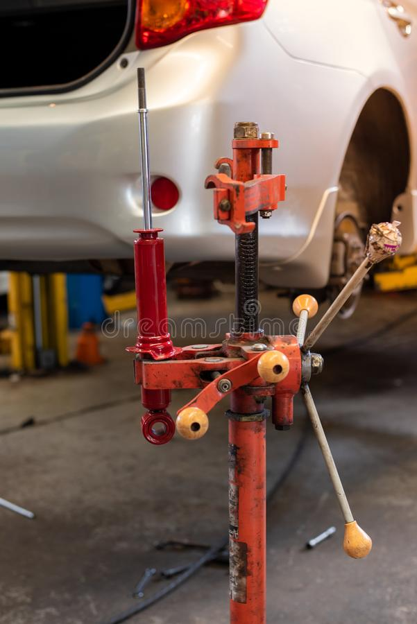 在红色机器的红色汽车吸收体吊在自动修理服务 免版税库存照片
