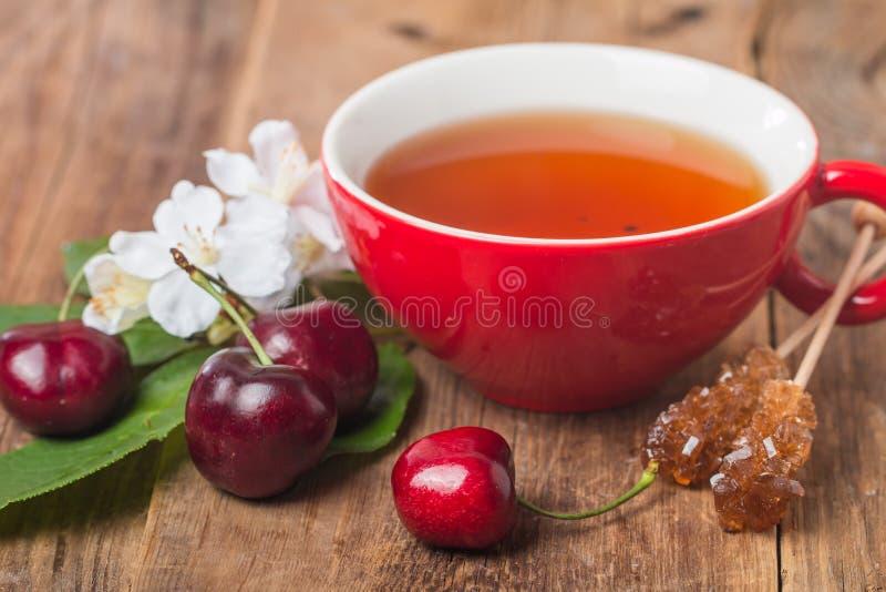 在红色杯子的黑人英语茶用樱桃 库存图片