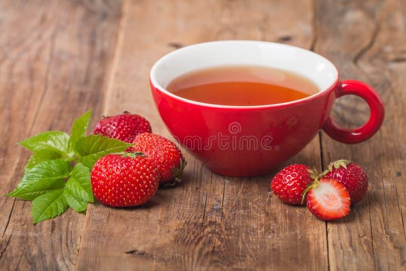 在红色杯子的黑人英语茶用草莓 免版税库存图片