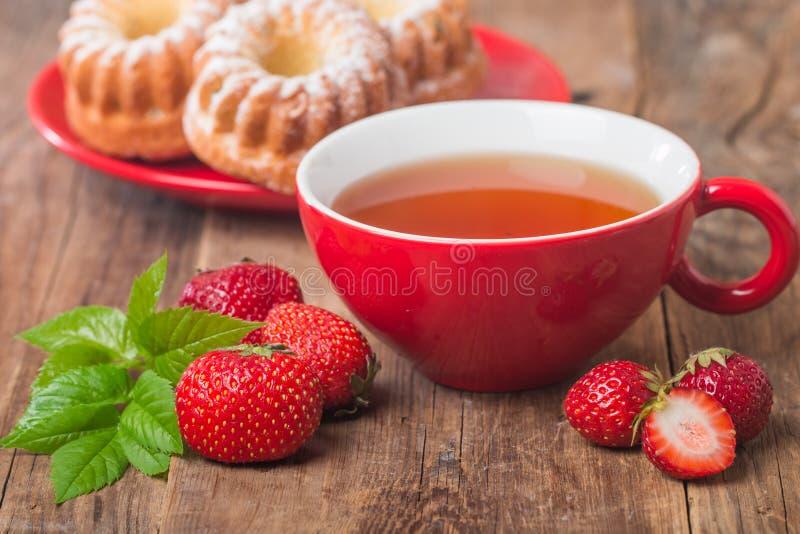 在红色杯子的黑人英语茶用草莓 库存图片