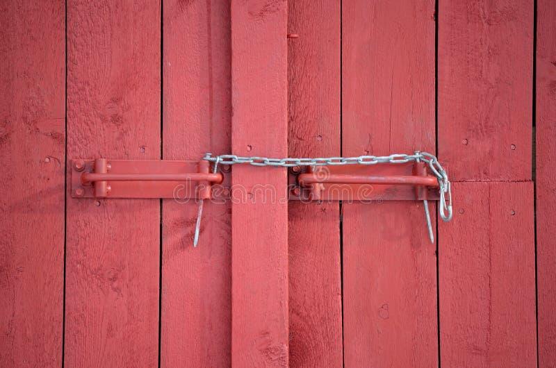 在红色毂仓大门的暂时链锁 免版税库存照片