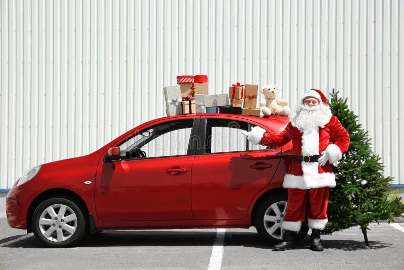 在红色汽车附近的地道圣诞老人有对此的礼物盒的` s上面 免版税库存图片