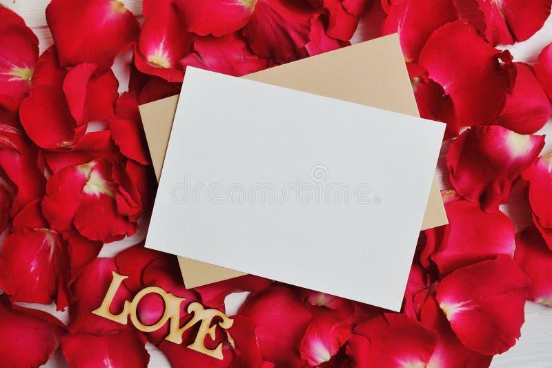 在红色玫瑰花瓣的大模型卡片为华伦泰` s天 平的位置,与一个地方的顶视图您的文本的 库存图片