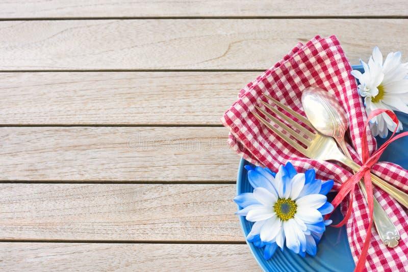 在红色白色和蓝色颜色7月4日庆祝的在木委员会背景表上与室或空间的野餐桌设置c的 免版税库存图片