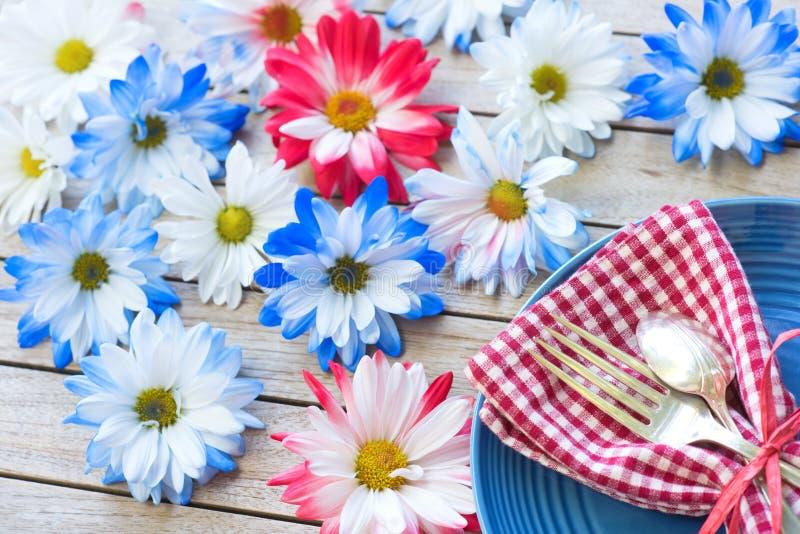 在红色白色和蓝色颜色7月4日庆祝的在木委员会背景表上与室或空间的野餐桌设置c的 库存图片