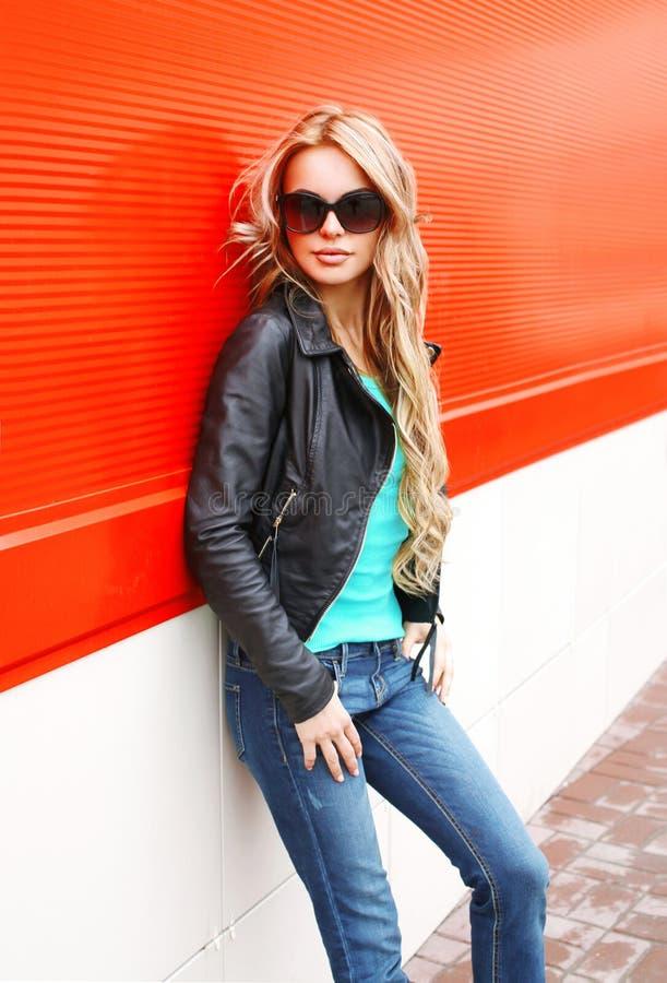 在红色的城市塑造黑岩石夹克太阳镜的白肤金发的妇女 库存照片