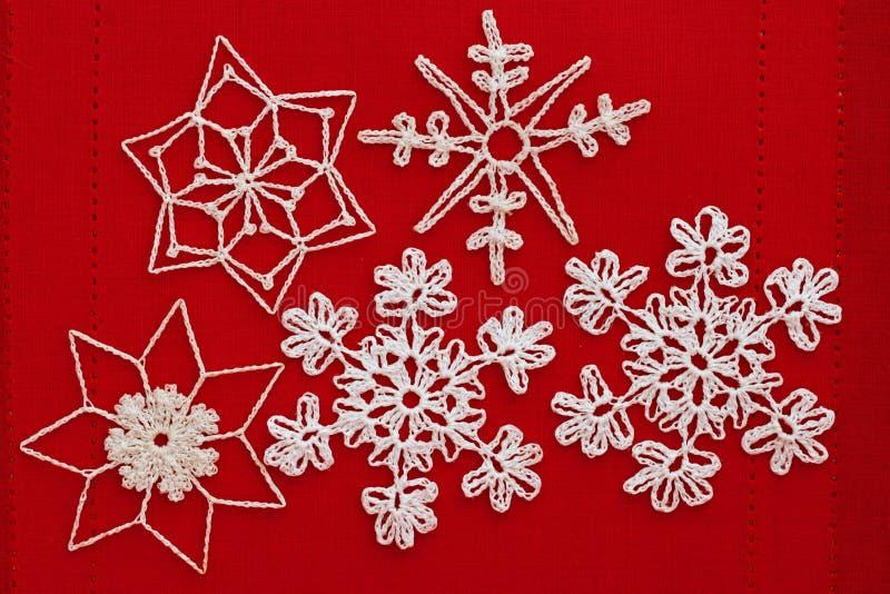 在红色的白色钩针编织的雪花 免版税库存照片