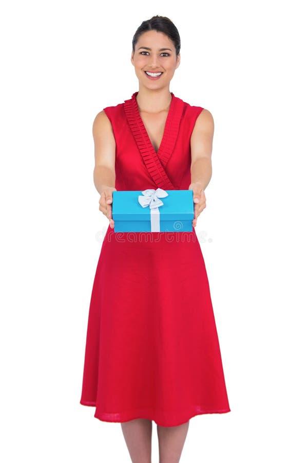 在红色礼服提供的礼物的愉快的迷人的模型 免版税库存图片