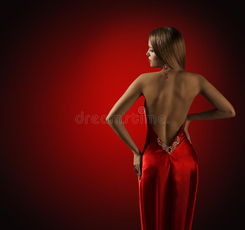 在红色礼服的妇女后面,美好的时装模特儿背面图 库存照片