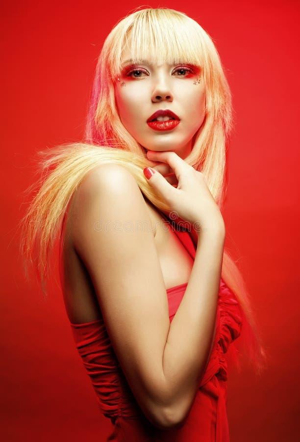 在红色礼服的完善的白肤金发的模型在红色背景 免版税库存图片