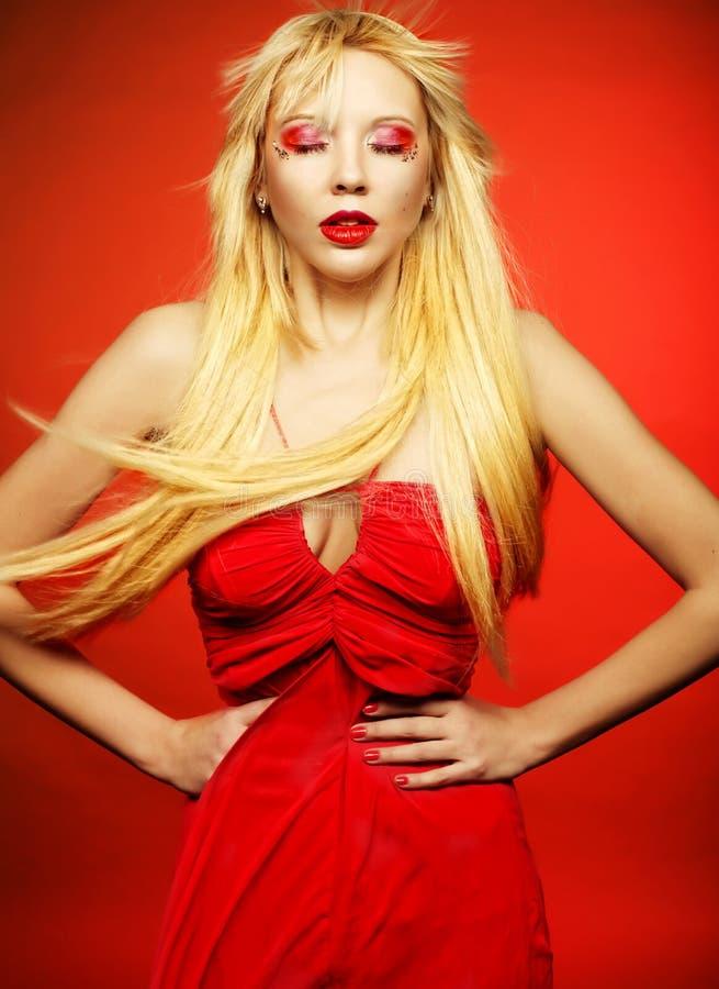 在红色礼服的完善的白肤金发的模型在红色背景 免版税图库摄影