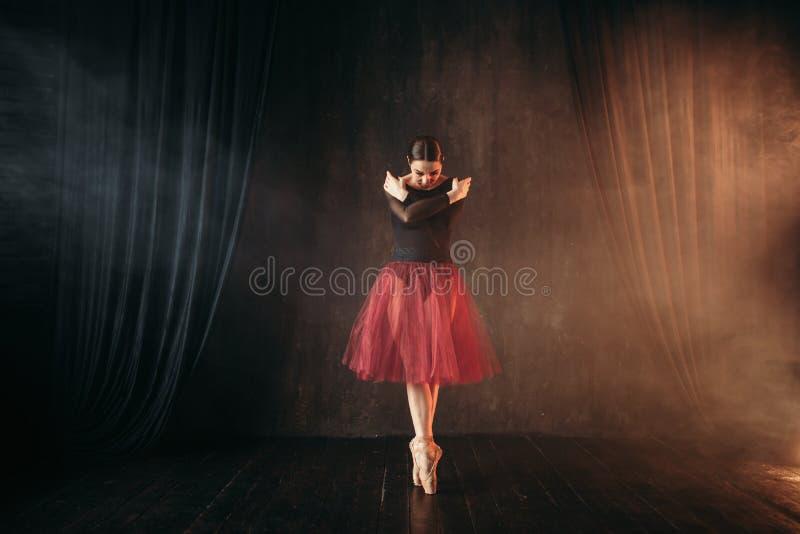 在红色礼服跳舞的跳芭蕾舞者在阶段 免版税库存照片