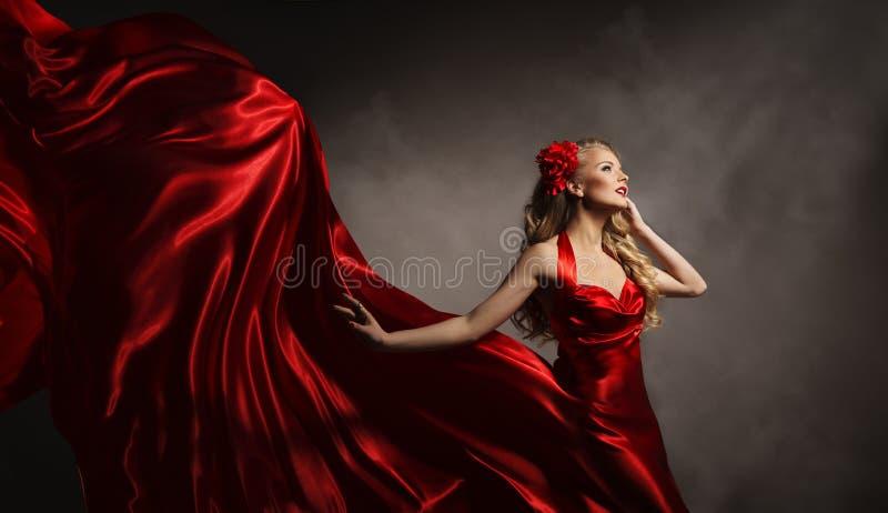 在红色礼服,摆在飞行丝绸布料的魅力妇女的模型 免版税库存照片
