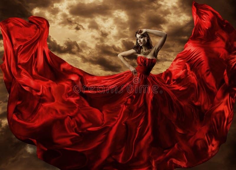 在红色礼服,时装模特儿舞蹈飞行褂子织品的妇女跳舞 免版税图库摄影