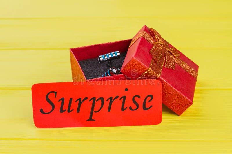 在红色礼物盒的金属圆柱形螺柱按钮 免版税图库摄影