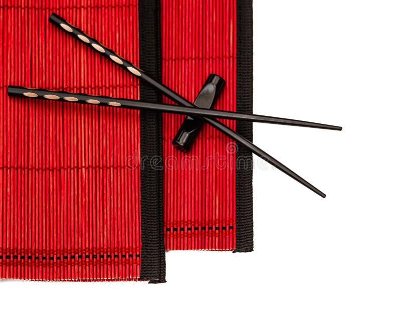 在红色竹席子的黑中国筷子 亚洲样式 免版税库存图片