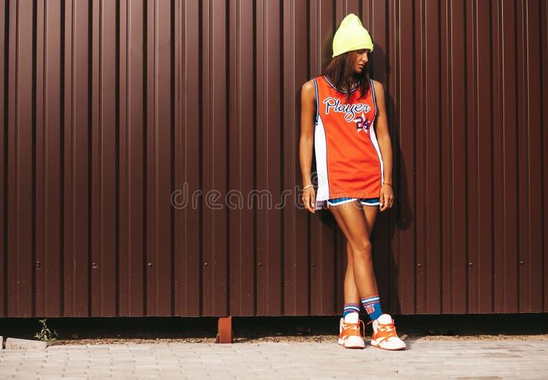 在红色篮球的美好的女孩模型在棕色金属墙壁附近炫耀摆在 免版税库存图片