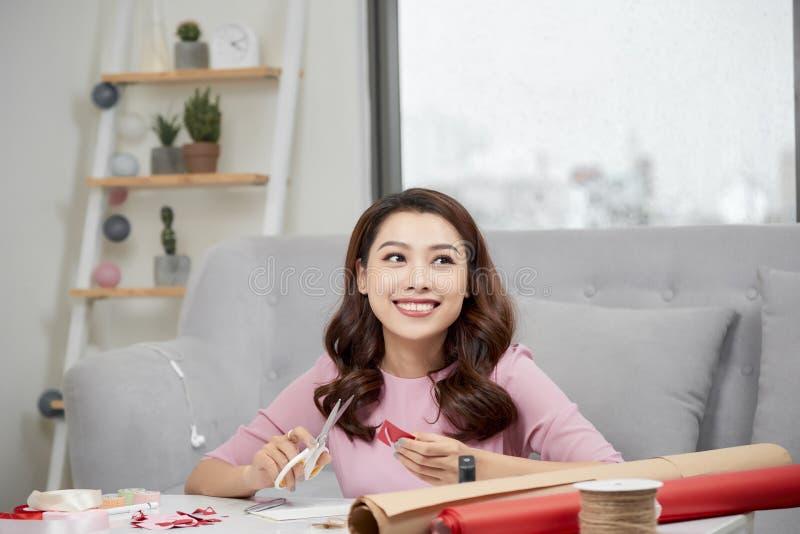 在红色纸外面的微笑的女孩切口华伦泰心脏与剪刀在客厅 库存照片