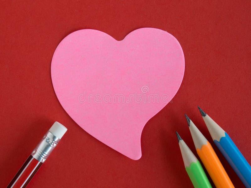 在红色纸的桃红色心形的备忘录与五颜六色的铅笔 免版税库存图片