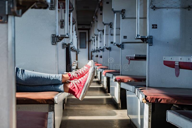 在红色网球鞋的妇女腿在葡萄酒空的列车车箱 fem 免版税库存照片