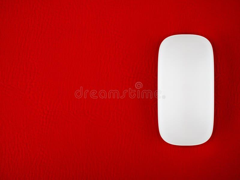 在红色老鼠爪纹理背景的一只白色计算机老鼠 库存图片