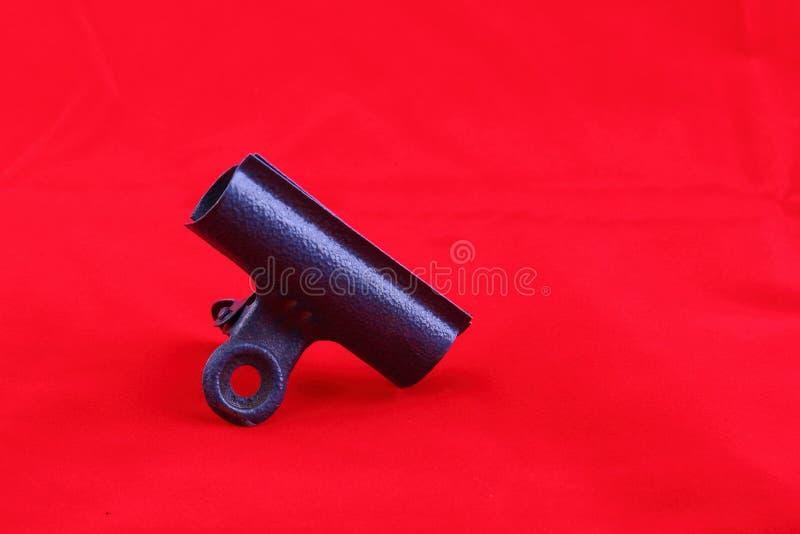在红色背景的减速火箭的金属夹子 免版税库存图片