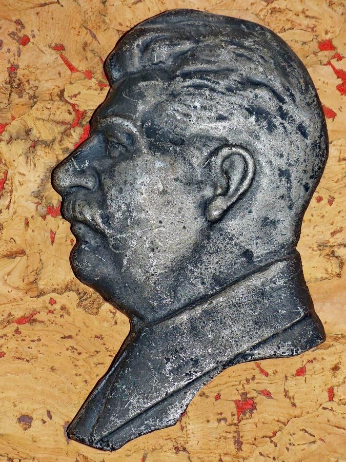 在红色背景的斯大林浅浮雕 斯大林-俄国革命家,苏联政治,状态、军事和党的领导 库存图片