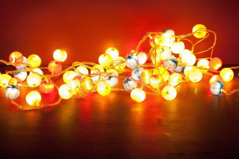 在红色背景的灼烧的圣诞灯 库存照片