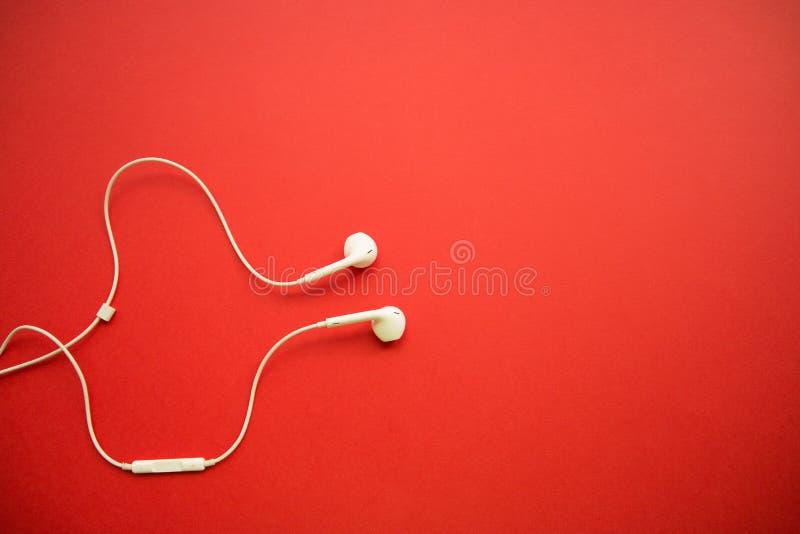 在红色背景的白色耳机与拷贝空间 免版税库存图片