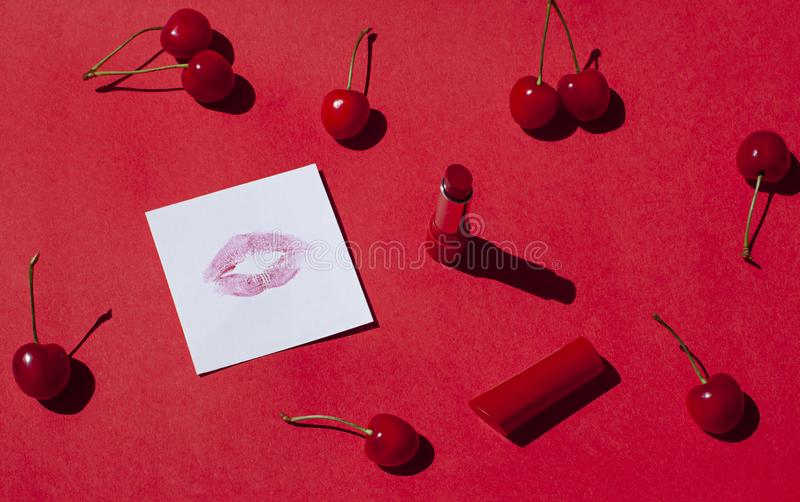 在红色背景的红色口红用成熟樱桃 免版税库存图片
