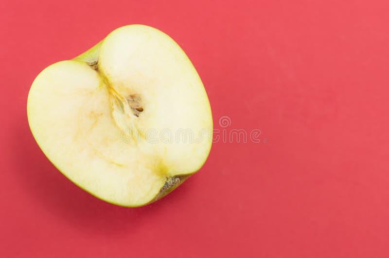 在红色背景的被对分的绿色苹果 库存照片