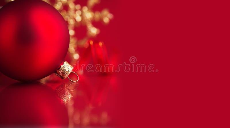 在红色背景的金黄和红色圣诞节装饰品与拷贝空间 免版税库存照片