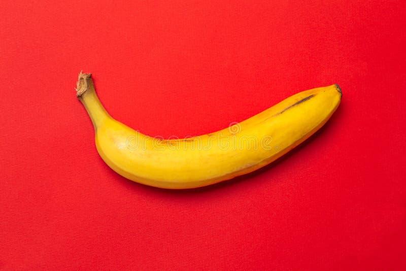 在红色背景的黄色新鲜的成熟有机香蕉 设计的现代最小的食物超现实主义想法 免版税库存图片