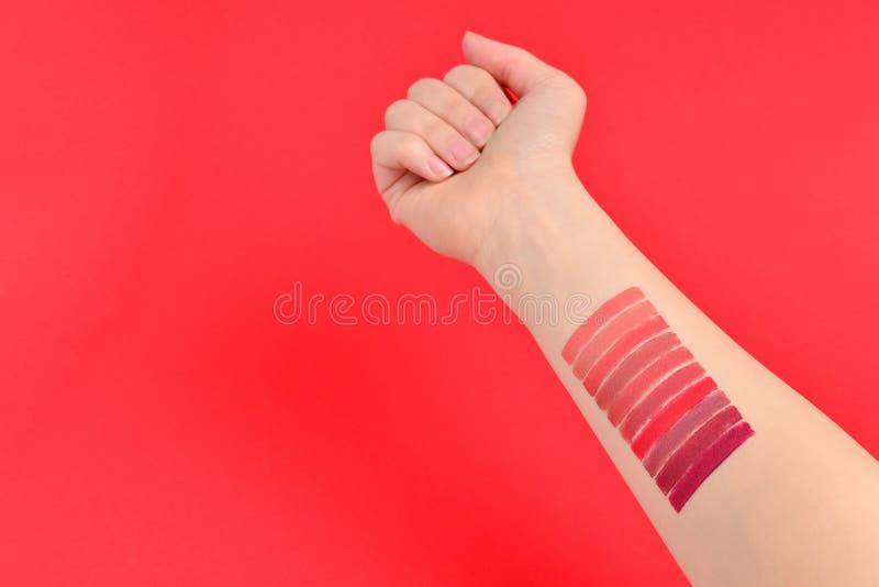 在红色背景隔绝的妇女手上的唇膏样片 库存照片